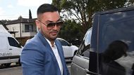 Former Auburn deputy mayor Salim Mehajer returns home as police continue to raid his home in Lidcombe, Sydney Wednesday, ...