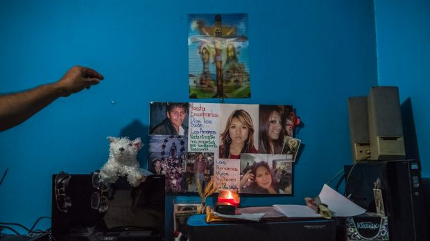 Carlos Saldana reaches to adjust the small shrine created in memory of his and Vicky Delgadillo's missing children, in ...