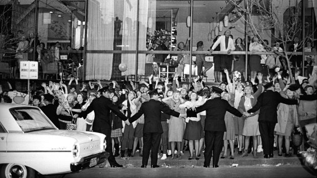 Police officers hold back the tide of fans screaming for the Beatles outside the Sheraton Hotel, where they stayed in ...