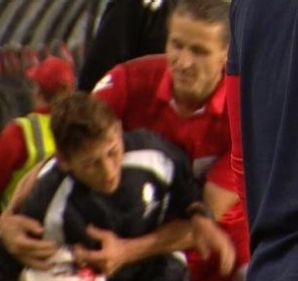 Adelaide United's Michael Marrone grabs a ball boy during the FFA Cup final against Sydney FC.