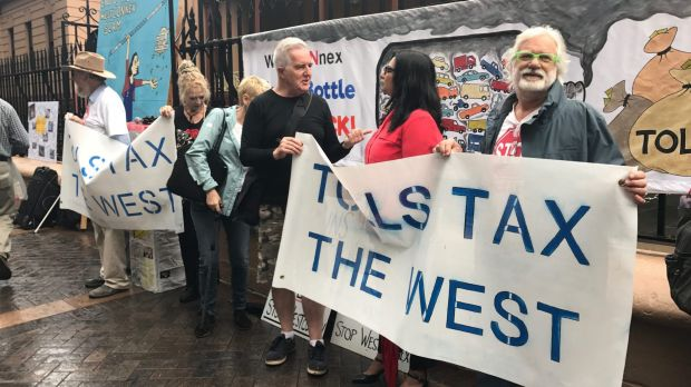 Protesters hold signs during a rally against the WestConnex road project outside the NSW parliament building in Sydney.