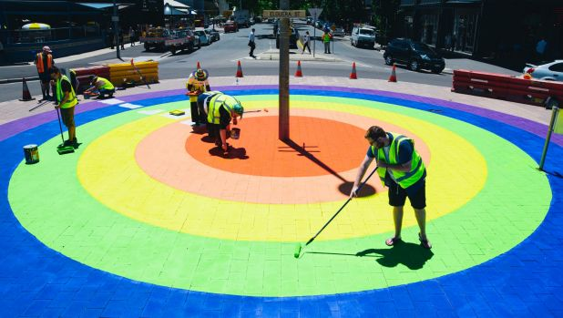 Members of the community paint the final touches on the rainbow roundabout on the corner of Elouera St and Lonsdale St ...