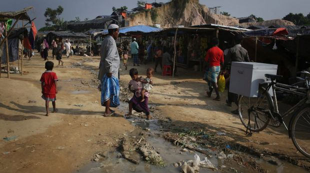 A Rohingya Muslim girl carries her baby sister as she walks across a stream of drainage water at the Thaingkhali refugee ...