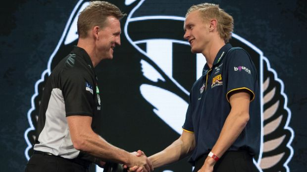 Jaidyn Stephenson of the Eastern Ranges is presented with his guernsey by Collingwood Magpies coach Nathan Buckley.