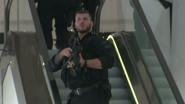 An armed police office patrols a department store on Oxford Street after reports of a shooting.