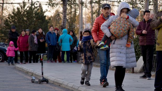 A woman carries a child as they arrive at the RYB kindergarten in Beijing, China, on Friday.