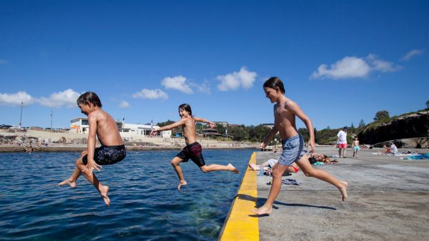 Crossing the line: (left to right) 10 year olds Bodie Taylor, Arki George, and Frankie Parsons jump in the ocean at Clovelly.