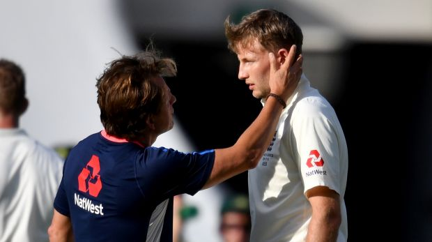 Joe Root is checked out by medical staff after being hit in the head.