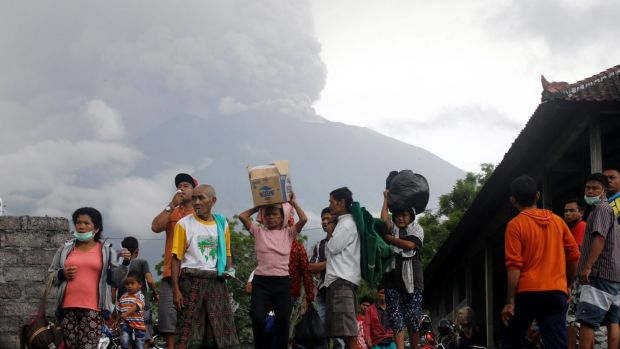Villagers carry their belongings during an evacuation following the eruption of Mount Agung.