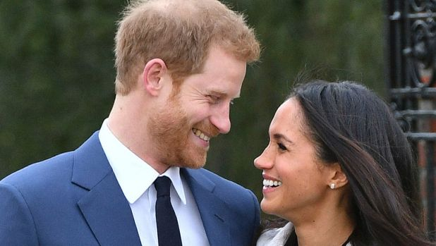 Britain's Prince Harry and Meghan Markle smile as they pose for the media in the grounds of Kensington Palace .
