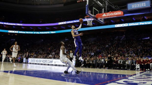 Philadelphia's Ben Simmons goes up for a dunk above Cleveland's JR Smith.