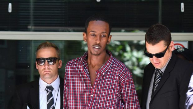 Ali Khalif Shire Ali is taken from the Australian Federal Police building to face court charged with terrorism offences.