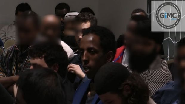 Ali Ali (centre) speaking about being followed by ASIO.