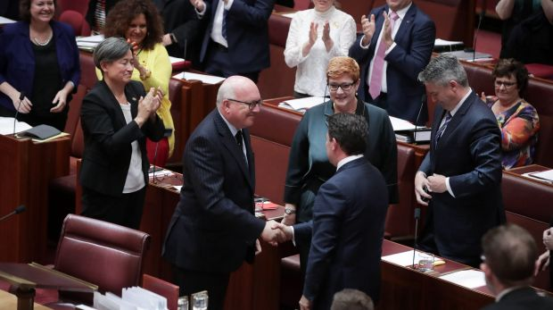 Attorney-General George Brandis shakes hands with Liberal senator Dean Smith as the bill passes the Senate.