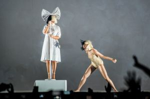 As she had in Melbourne, Sia stood still in the background and sang over a tape of her greatest hits for 90 minutes ...
