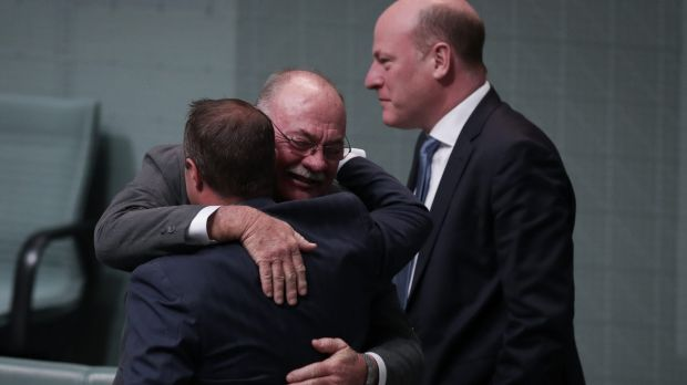 Government gay marriage supporters Tim Wilson and Warren Entsch embrace as Trent Zimmerman watches on.