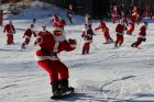 A snowboarder dressed as Santa Claus rides down a slope at Sunday River during the ski resort's 18th annual Santa Sunday ...