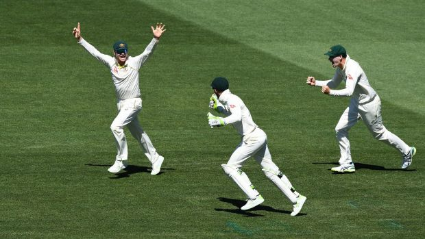 Victory march: Steve Smith, Tim Paine and Peter Handscomb celebrate the final wicket.