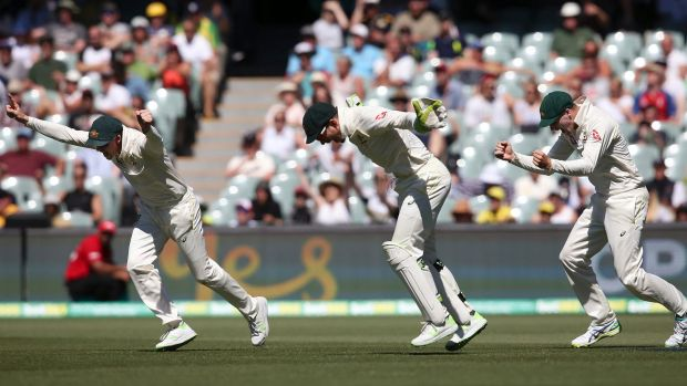 Australia's Steve Smith, left, Tim Paine and Peter Handscomb, right celebrate the fall of the last English wicket at the ...