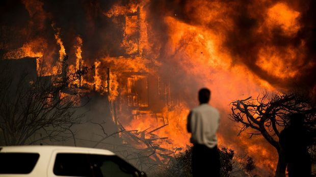 A man watches flames consume a residence as a wildfire rages in Ventura, California.
