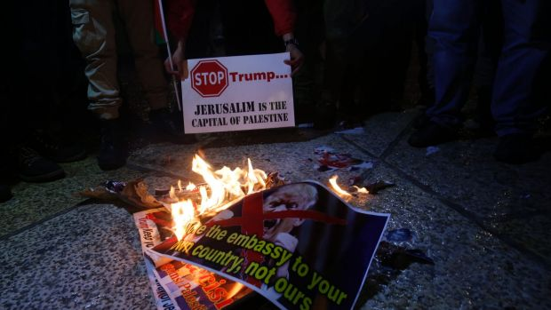 Palestinian burn a poster of the US President Donald Trump during a protest in Bethlehem, West Bank.