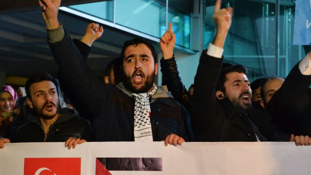 Holding a banner with a Turkish, left and a Palestinian flag, right, protesters chant anti-US slogans during a ...