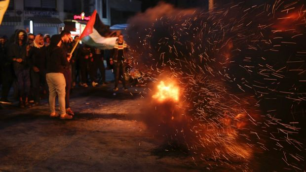 Palestinian protesters burn tires as they wave their national flags during a protest at the main square in Gaza City.
