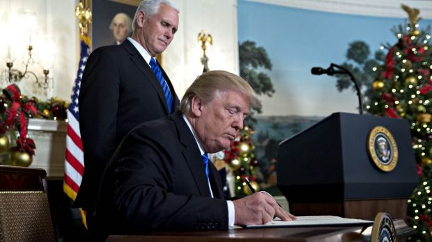 US President Donald Trump signs the proclamation next to US Vice-President Mike Pence.