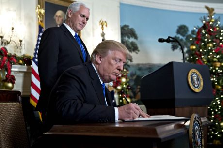U.S. President Donald Trump signs a proclamation next to U.S. Vice President Mike Pence, left, after making a statement ...