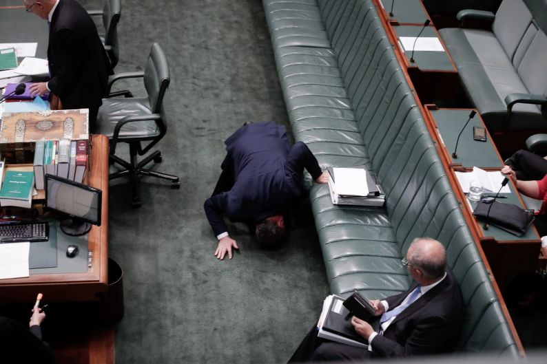 Deputy Prime Minister Barnaby Joyce looks for something under the frontbench as he arrives for Question Time at ...