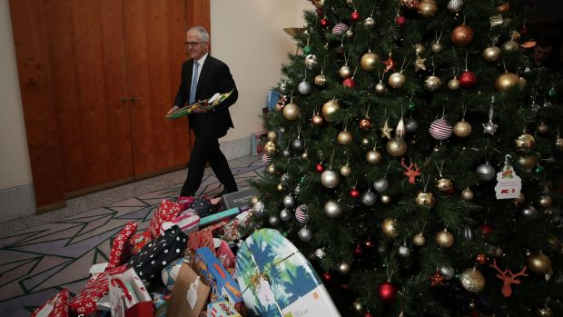 Prime Minister Malcolm Turnbull helps load the van with gifts from the Kmart Wishing Tree on Thursday.