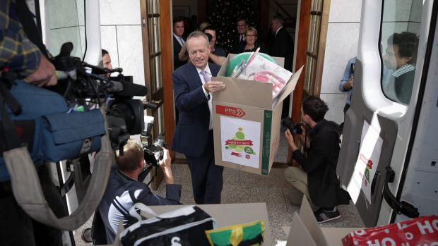 Opposition Leader Bill Shorten helps load the van with gifts from the Kmart Wishing Tree at the Prime Minister's office ...