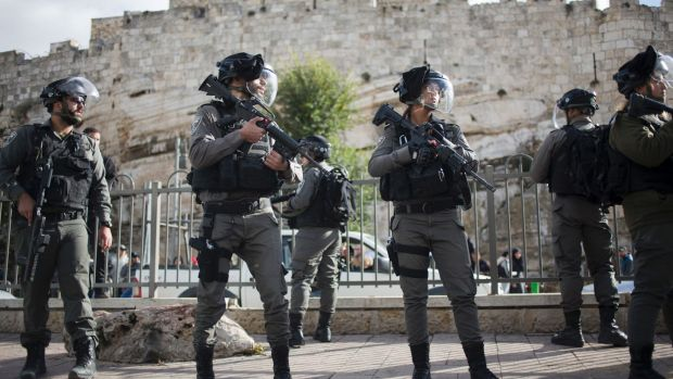 Israeli police officers stand guard as Palestinian women protest outside the Damascus Gate in Jerusalem Old City.