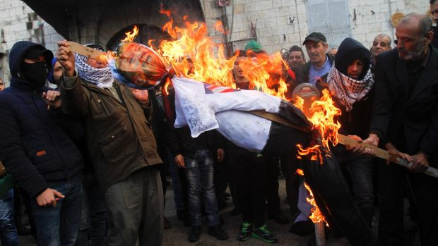 Palestinian protesters burn an effigy of US President Donald Trump during a protest against the decision to recognise ...
