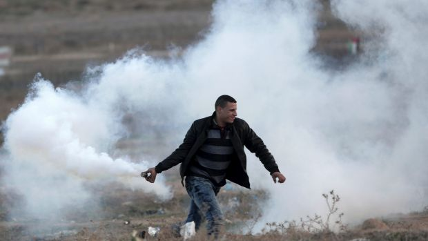 A Palestinian protester prepares to throw back a teargas canister that was fired by Israeli soldiers, during clashes on ...
