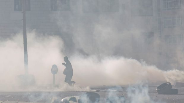 A Palestinian protester runs amid tear gas during clashes with Israeli troops following protests against U.S. President ...