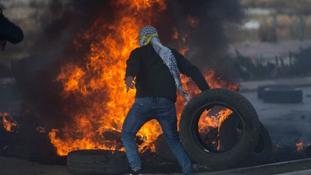 A Palestinian protester burns tires during clashes with Israeli troops.