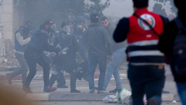 Journalists evacuate an injured Palestinian protester toward an ambulance during clashes with Israeli troops following ...