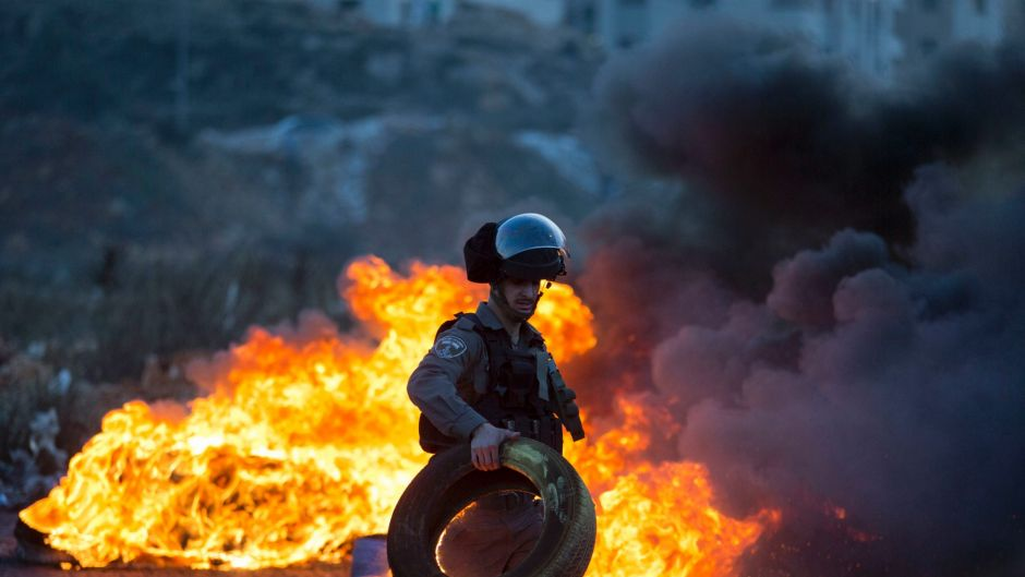 Israeli border police officer clears a burning tire during clashes with Palestinian protesters following protests ...