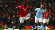Manchester United's Romelu Lukaku fights for the ball with Manchester City's Nicolas Otamendi, left, and Fabian Delph ...