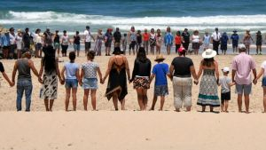 People gather on Lighthouse Beach near Port Macquarie to show support for the family of an 11-year-old boy from the ACT ...