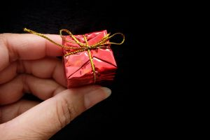 red Christmas present on a black background. Christmas gift generic image. Photo: Shutterstock