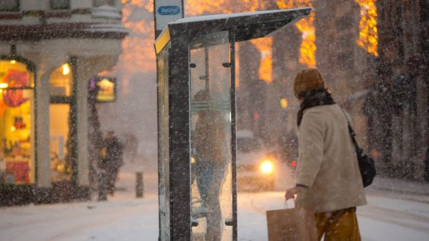 A woman takes cover from the snow at a tram stop as shopper crosses the street as snow covers the city of Amsterdam, ...