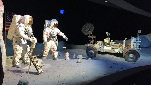 A scene on the Moon, with two astronauts alongside a lunar rover.