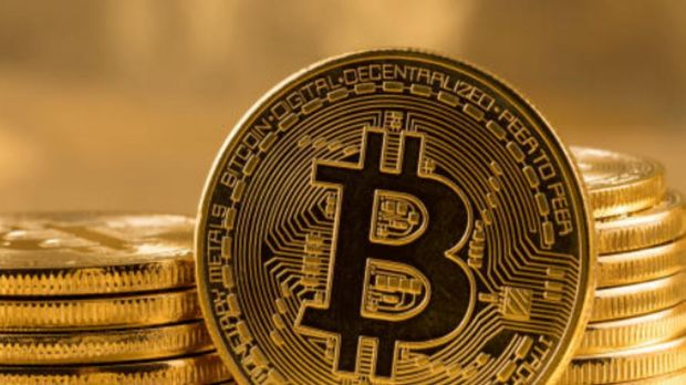 Bitcoin / Bitcoins. Generic. Photo by?Steve Heap. Stack of bitcoins with gold background with a single coin facing the ...