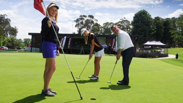 Member for Monaro and Deputy Premier of NSW, John Barilaro, tests his putting skill against sisters Chloe, (on the left ...