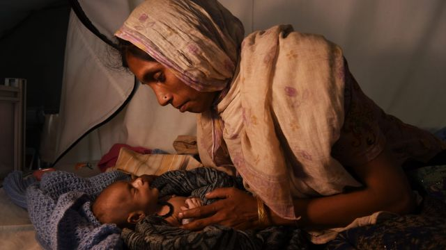 Rohingya woman Laila Begum holds her son Mohammed Ifran's hand as he receives treatment at the Red Cross Field Hospital ...