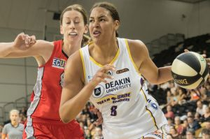 Fast break: Melbourne's Liz Cambage strides past Perth's Natalie Burton at the State Basketball centre on Sunday.