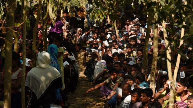 Rohingya refugees sit in a queue at a Red Cross distribution point.