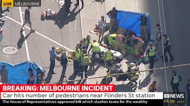 Emergency services tend to pedestrians outside of Flinders Street Station.
